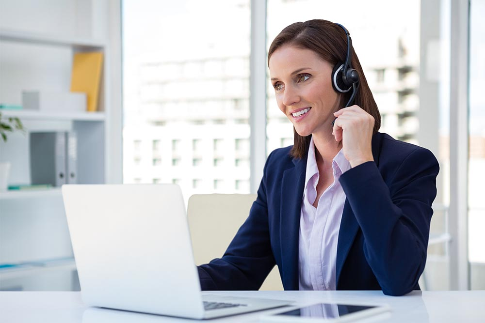 Lady with headset on in front of laptop